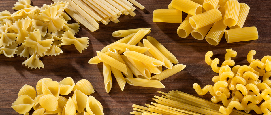 Uncooked groups of pasta on cutting board with bowtie. fettuccini, shell, rigatoni, cavatappi and spaghetti pasta types