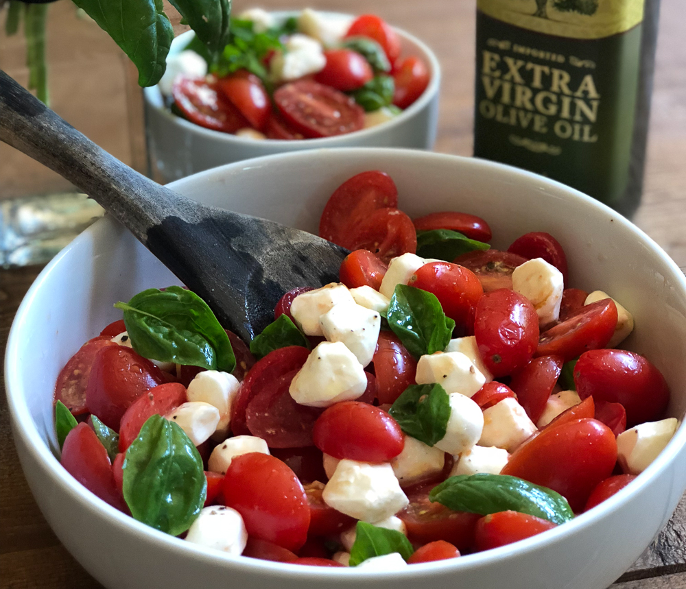 Caprese Salad in bowl with wooden serving spoon
