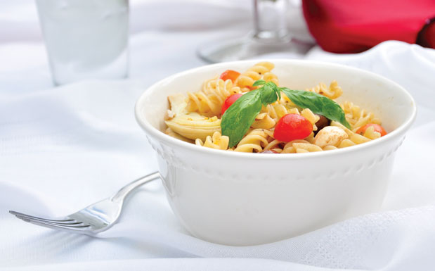 Bowl of pasta salad on white table cloth