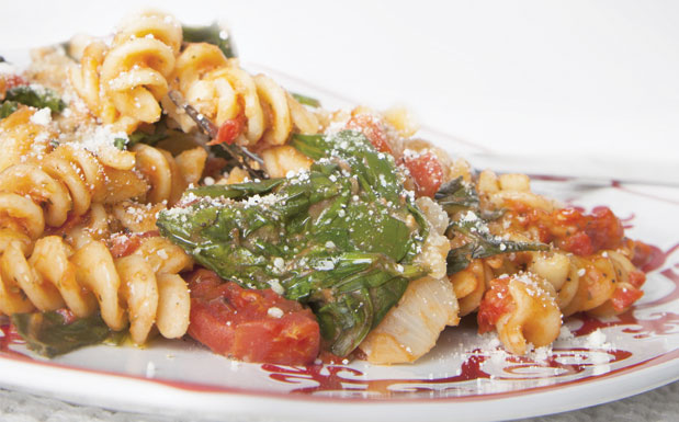 Close up of fusilli pasta with spinach and grated cheese