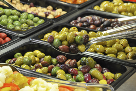Olives in deli area with spoon scooping them up