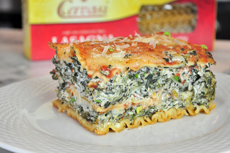 Slice of spinach lasagna on white plate