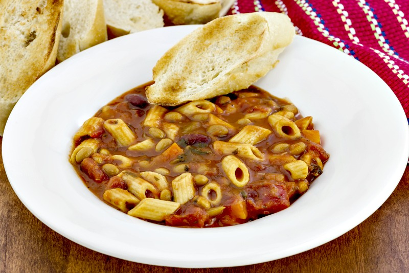Pasta soup in white bowl with piece of toasted bread
