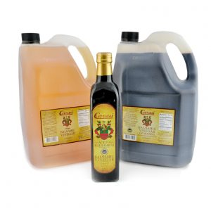 Two jugs and one retail bottle of Cervasi Balsamic Vinegar