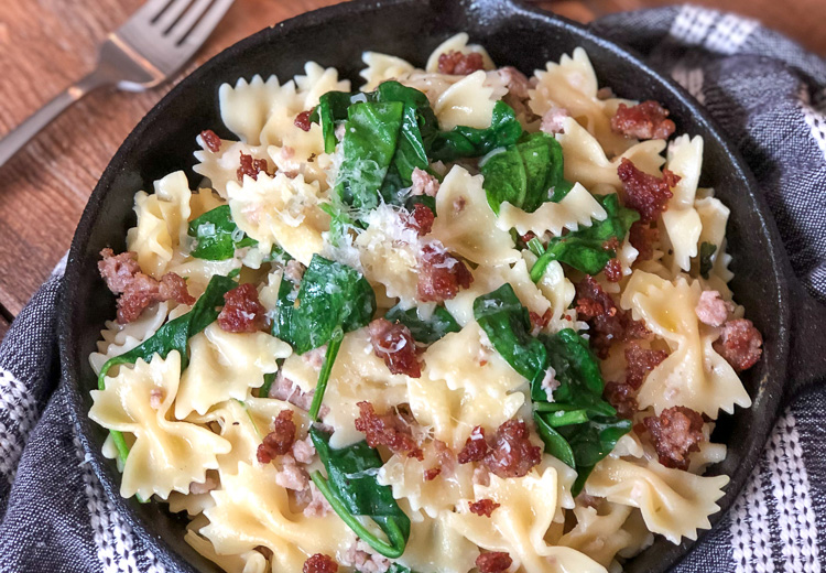 Farfalle (bowtie) pasta with spinach, sausage and cheese in a skillet